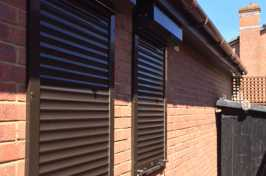 brown roller shutters over two single windows