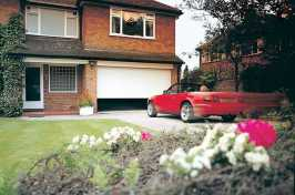 large roller garage door with red sports car driving up to it