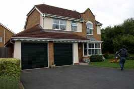 two single roller garage doors on a detached suburban house