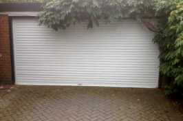 white roller garage door covered by foliage