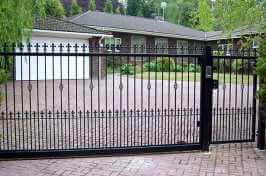 ornate bespoke driveway gate with matching side gate and intercom system