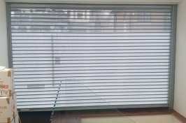 Perforated electric roller shutter in office